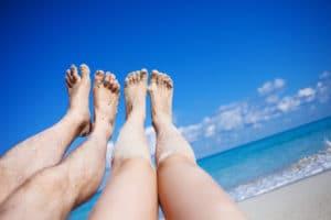 photo de dos pares de piernas alzadas al cielo en la playa