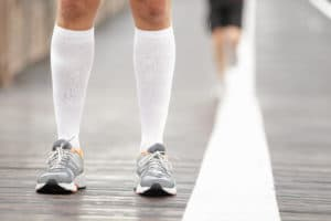 Running shoes closeup and compression socks  on a person on pavement or a sidewalk