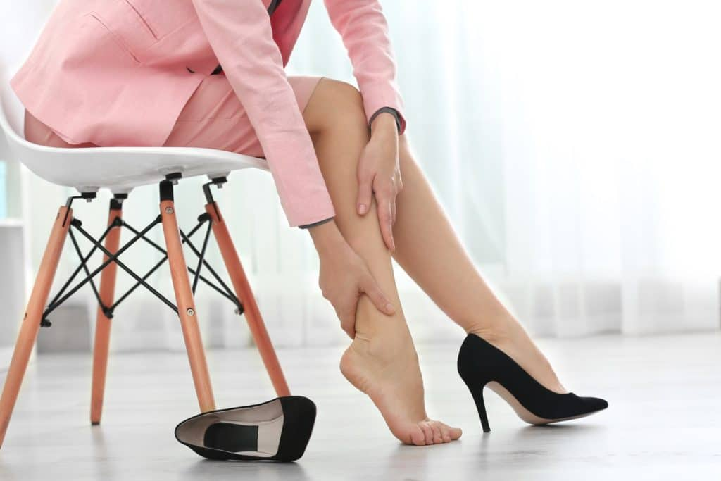 woman massaging her ankle with a black heel discarded
