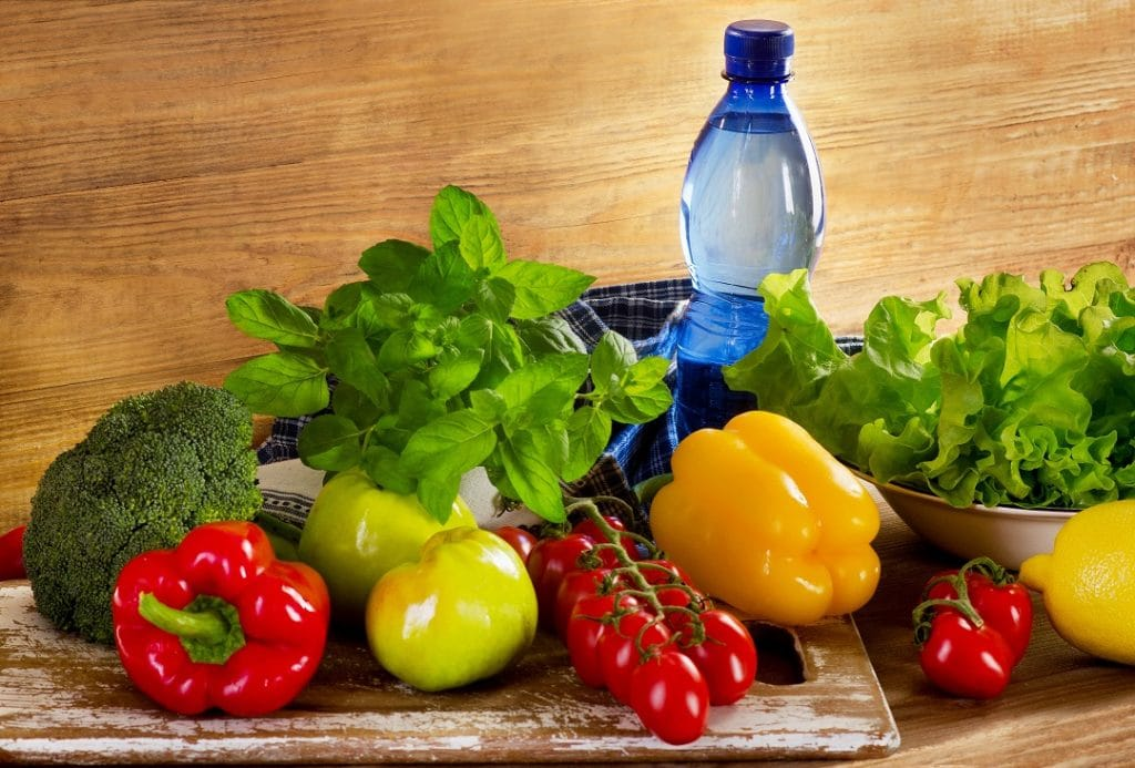 Fresh organic vegetables with bottle of water - health and diet concept